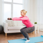 smiling woman with dumbbells exercising at home
